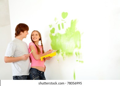 Young happy couple painting walls in new house