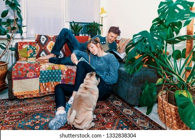 young happy couple with pet at home reading books - lifestyle, leisure, life together concept