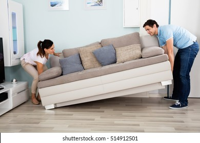 Young Happy Couple Placing Sofa Together In Living Room At Home