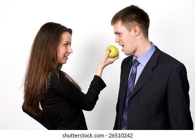 Young happy couple playfully eating apple