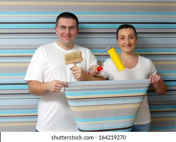 Young happy couple posing against papered wall holding some basic wallpapering tools