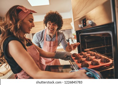 Young happy couple pulling baked muffins from the oven.