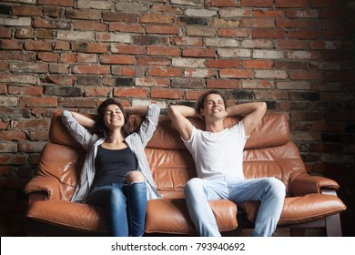 Young happy couple relaxing on comfortable leather couch at home, relaxed smiling man and woman resting on sofa in loft interior breathing fresh air meditating together, no stress, positive thinking
