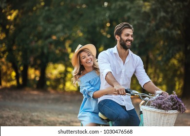 Young happy couple riding a bicycle in the park