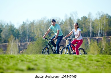 A young happy couple riding bicycles together