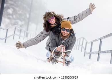 Young happy couple riding sled in snow