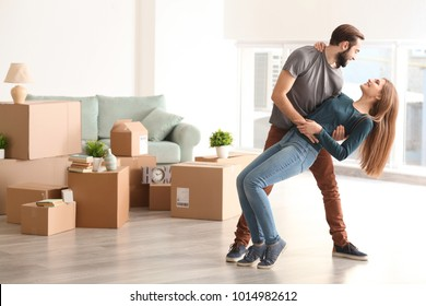 Young happy couple in room with moving boxes at new home