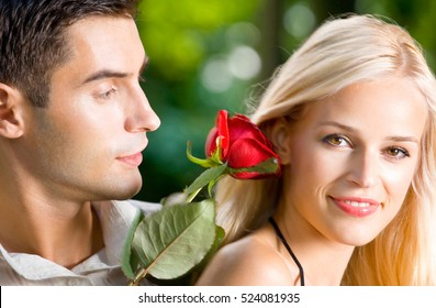 Young happy couple with rose, outdoors. Love, flirt, romantic, relations theme concept.
