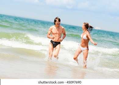Young happy couple running in the ocean waves