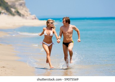 Young happy couple running on the beach