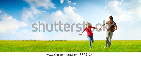 Junge glückliche Paare, die auf einer grünen Wiese mit blauem bewölktem Himmel auf dem Hintergrund laufen