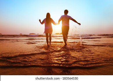 young happy couple running to the sea at sunset beach