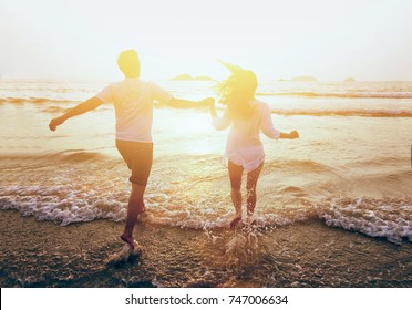 young happy couple running to the sea on the beach, summer holidays travel