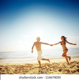 Young happy couple running together among a beach at sunny day