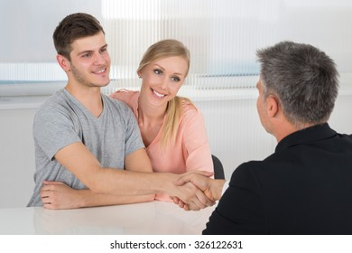 Young Happy Couple Shaking Hands With Male Agent In Office