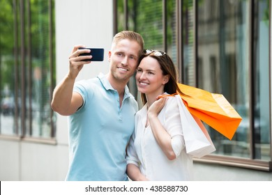 Young Happy Couple With Shopping Bag Taking Picture In Smartphone