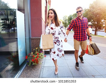 Young happy couple with shopping bags in the city