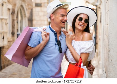 Young happy couple with shopping bags in the city enjoying summer vacation