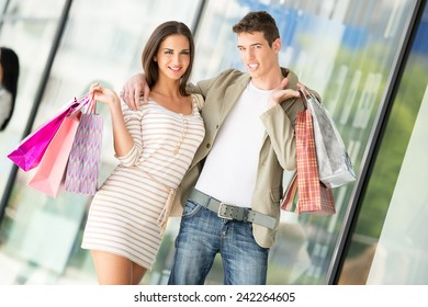 Young happy couple in shopping passes in front of window shopping mall carrying bags in their hands.