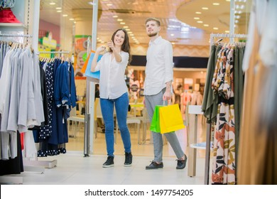 young happy couple shopping together clothes at fashion shop