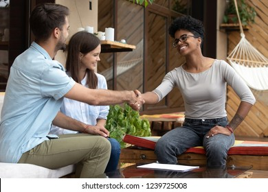 Young happy couple signing contract with realtor or wedding planner in cafe, excited man shaking hand of African American female financial advisor, mortgage agreement, good deal, happy clients