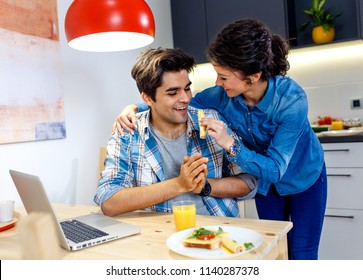Young happy couple sitting by table in apartment and having breakfast together.