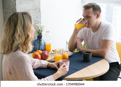 Young happy couple sitting by table in modern apartment and having breakfast together