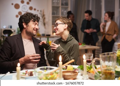 Young happy couple sitting at the holiday table with wine glasses and talking during party at home