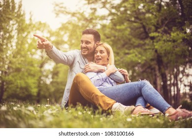 Young happy couple sitting on grass and talking. Boyfriend showing something to his girlfriend.