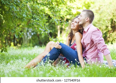 Young happy couple sitting on ground enjoying spring in the park