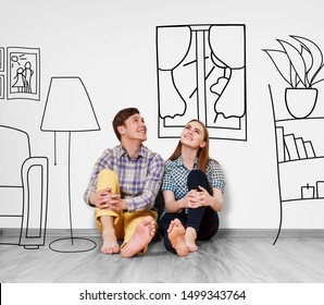 Young happy couple sitting on the floor in their new flat among painted furniture on the wall.