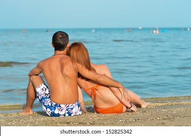 Young happy couple sitting on sandy beach and embracing outdoor