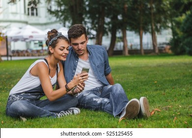 Young happy couple sitting on grass and and looking on smartphone display