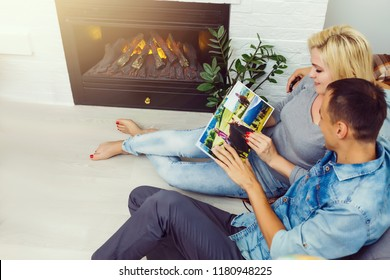 Young Happy Couple Sitting Side By Side On Sofa Looking At Photo Album