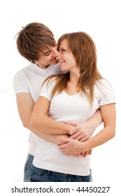 Young happy couple smiling and cuddling. Casual wear. Isolated over white
