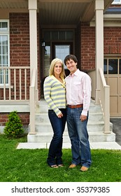 Young happy couple standing in front of house