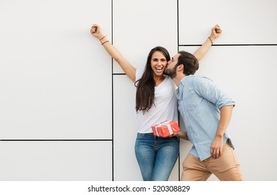 young happy couple standing outside, man offering a gift to his girlfriend and making her very happy