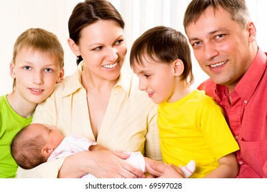 young happy couple standing with three children