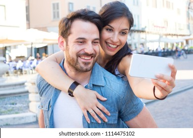 Young happy couple taking a selfie with smartphone and and discovering the city