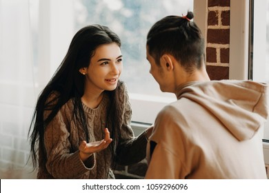 Young happy couple talking in a cafe