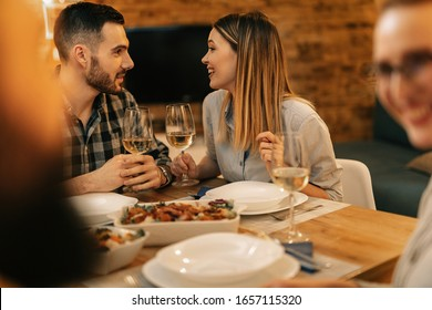 Young happy couple talking to each other while drinking wine and having dinner with friends at dining table.