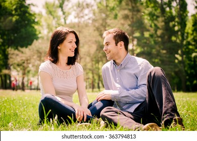 Young happy couple talking together outdoor - sitting on grass in nature