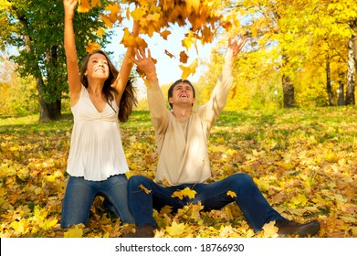 """Young happy couple throwing autumn leaves in the air. Keyword for this collection is """"autumn08"""""""