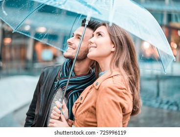 Young happy couple under the rain day covering with transparent umbrella in city center - Lovers traveling Europe during fall season - Love concept - Focus on woman face - Teal and orange filter