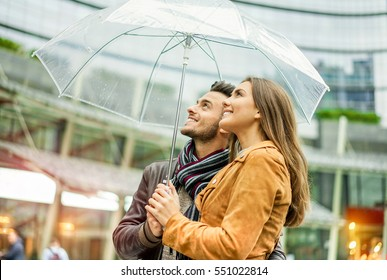 Young happy couple under soft raining day covering with transparent umbrella in london city center - Lovers enjoying vacation together - Love concept - Focus on woman face - Warm filter