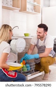 Young happy couple unloading dishwasher with clean crockery. Working together and helping each other in housework