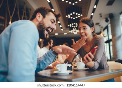 Young happy couple usinf smartphone in cafe