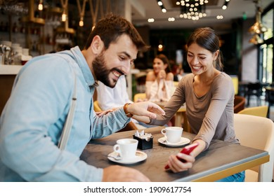 Young happy couple using smartphone in cafe