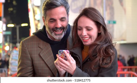 Young happy couple viewing smart cell phone in Times Square New York at night. Share memories and pictures on social media with online mobile  app