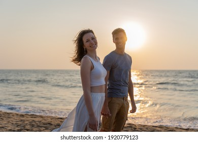 Young happy couple walking on the beach during sunset